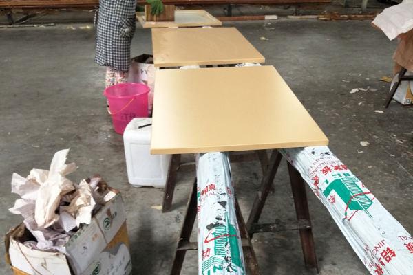 工人在润湿的铝板上贴木纹转印膜